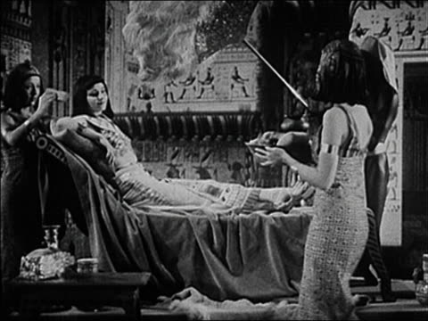 1940 medium shot actress as cleopatra reclining and being served fruit + fanned by servants - queen royal person stock videos & royalty-free footage