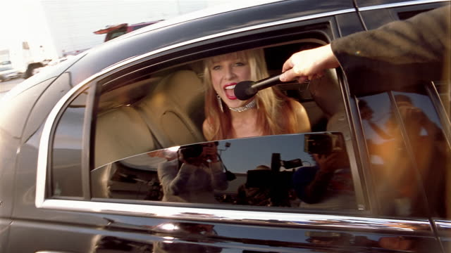 Medium shot actress in limousine smiling and waving / pushing away microphone + yelling at press