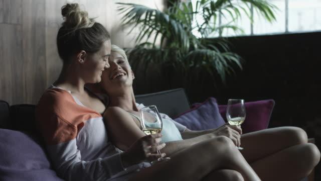 vídeos y material grabado en eventos de stock de medium shot, affectionate lesbian couple drink white wine - camisola