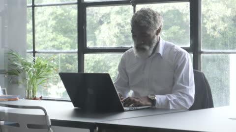 medium shot, african american businessman in office - skjorta bildbanksvideor och videomaterial från bakom kulisserna