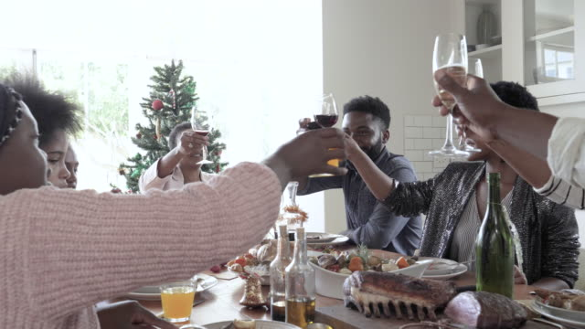 medium shot, african american family cheers on christmas day - meal stock videos & royalty-free footage