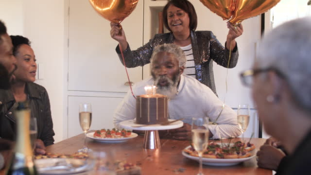 medium shot, african american man blows out candles - happiness stock videos & royalty-free footage