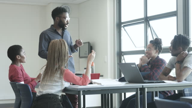 medium shot, african american professor helps students - soft focus stock videos & royalty-free footage