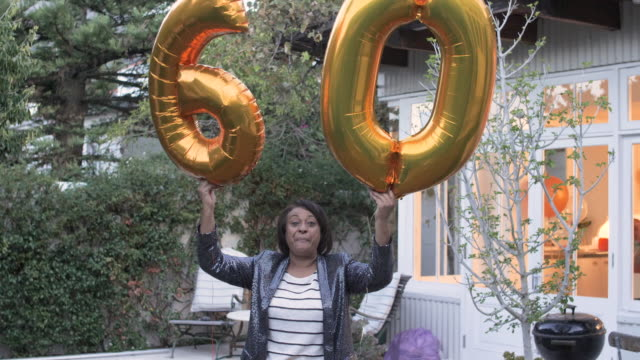 medium shot, african american woman holds birthday balloons - life events stock videos & royalty-free footage