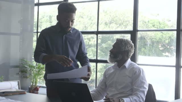 medium shot, african american workers look over paperwork - document stock videos & royalty-free footage