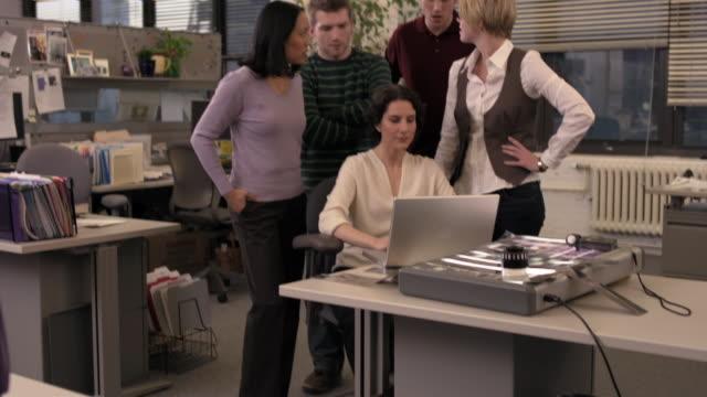 vídeos de stock, filmes e b-roll de medium shot african violet on desk/ tilt up office staff looking at laptop over manager's shoulder - mãos cobrindo boca
