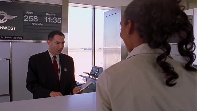 Medium shot airline worker checking passenger in at gate