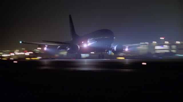 vidéos et rushes de medium shot airplane landing on runway at night surrounding by lights - atterrir