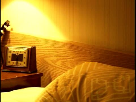 Medium shot Alarm clock and lamp sitting on nightstand in motel room