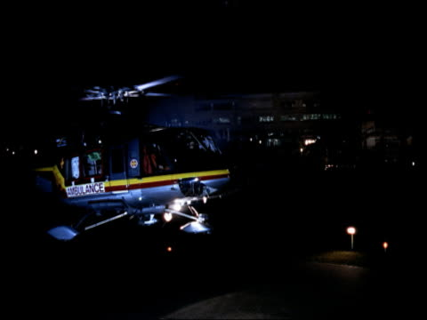 medium shot ambulance helicopter landing on roof of hospital at night - helicopter landing stock videos and b-roll footage