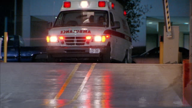 Medium shot ambulance turning onto street with lights flashing