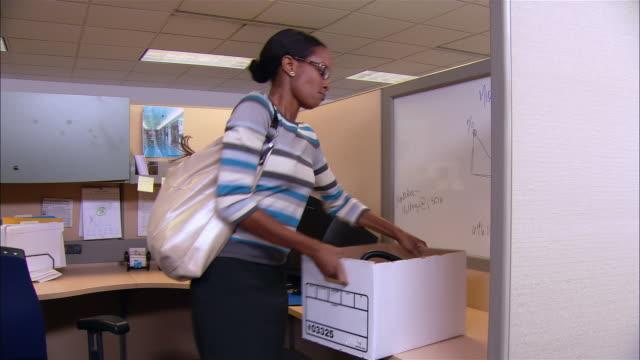 vídeos y material grabado en eventos de stock de medium shot angry woman carrying cardboard box after being terminated / walking past co-workers in cubicles - cambio de oficina