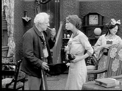 1913 B/W Medium shot Angry woman shouting at old man and telling him to leave after she finds his liquor bottle in living room / USA