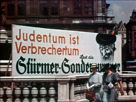 1938 medium shot antisemitic billboard sign w/caricature of jewish man / austria - anno 1938 video stock e b–roll