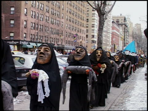 vídeos de stock, filmes e b-roll de medium shot antiwar protestors in masks and with blood on their hands carrying mock corpses / new york city - braço humano