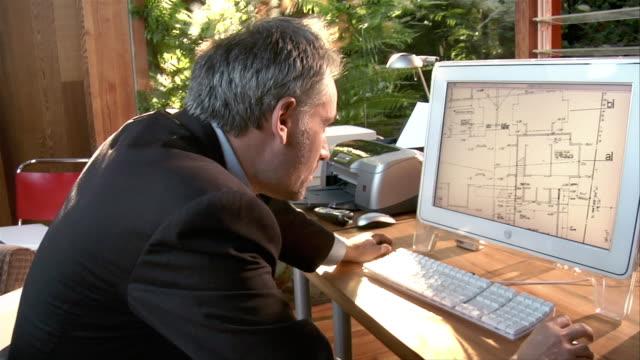 Medium shot architect looking at blueprint on computer
