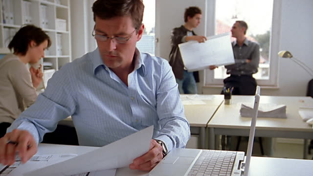 medium shot architect working in office / others working in background - 45 49 anni video stock e b–roll