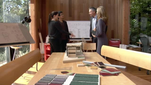 vídeos de stock e filmes b-roll de medium shot architects greeting client and showing building model to them - sentar se