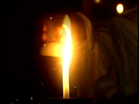 medium shot arm holding beaker over bunsen burner - bunsen burner stock videos & royalty-free footage