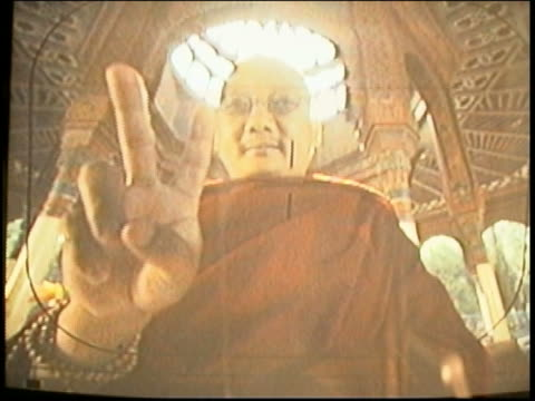 Medium shot Asian actor dressed as monk in video monitor giving peace sign to camera / director advises actor