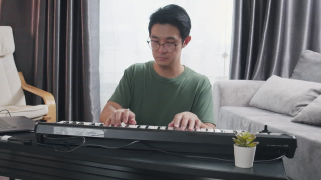 medium shot asian adult male playing keyboard piano in the living room at home. a man pianist playing or recording music to laptop computer. musician writing music by using electric keyboard - musician stock videos & royalty-free footage