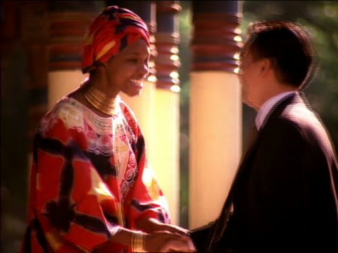 medium shot asian businessman and black woman shaking hands + bowing to one another outdoors / mexico city - inchinarsi video stock e b–roll