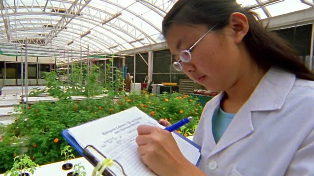 vídeos y material grabado en eventos de stock de medium shot asian female technician writing in notebook in green house - toma mediana