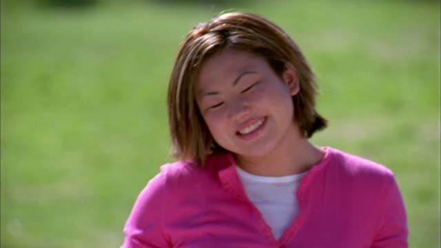 medium shot asian girl smiling at cam - una ragazza adolescente video stock e b–roll