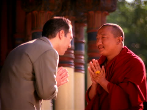 vídeos y material grabado en eventos de stock de medium shot asian male monk and hispanic businessman bowing to each other + talking / man talking on cell phone - hermanos