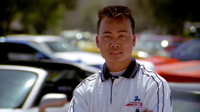 Medium shot Asian man w/arms crossed smiling w/cars parked in lot in background