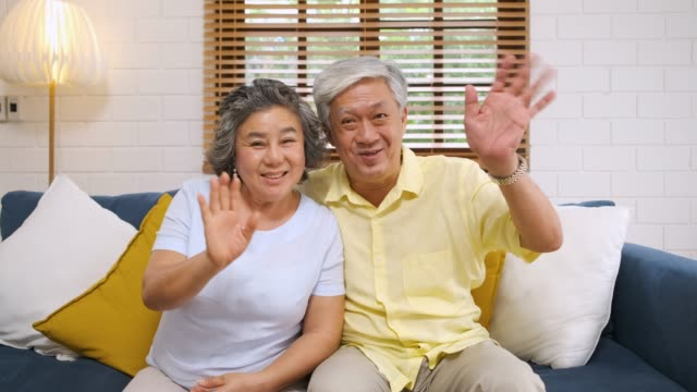 medium shot asian senior couple having video call from daugther and son in living room at home. technology lifestyle.aging at home - senior couple stock videos & royalty-free footage