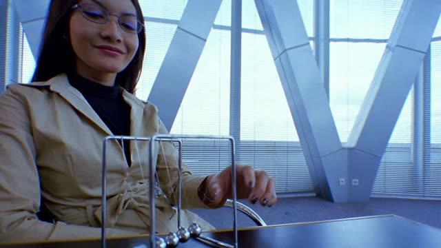 stockvideo's en b-roll-footage met medium shot asian woman hitting balls on newton's cradle desk toy in office - slinger van newton