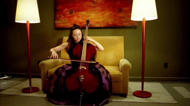 vidéos et rushes de medium shot asian woman playing cello on yellow sofa / looking at cam / seattle, washington - violoncelle