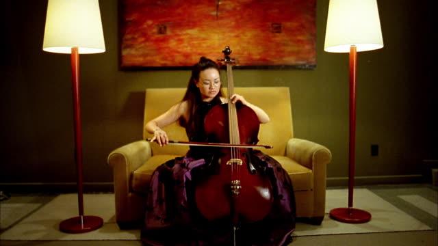 vidéos et rushes de medium shot asian woman playing cello / smiling at cam / seattle, washington - violoncelle
