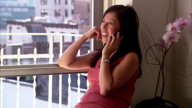 vídeos de stock e filmes b-roll de medium shot asian woman sitting on windowsill and talking on telephone - peitoril de janela