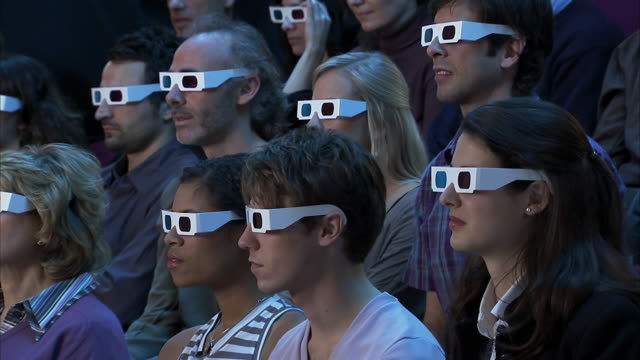 medium shot audience wearing 3-d glasses reacting to movie out of frame with shock and pleasure - 3d glasses stock videos & royalty-free footage
