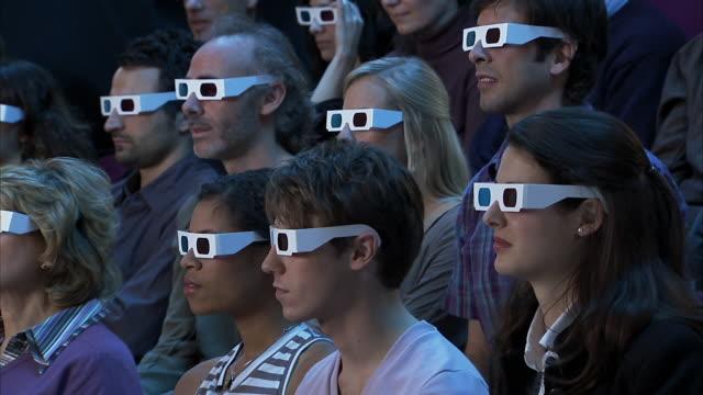 vídeos de stock, filmes e b-roll de medium shot audience wearing 3-d glasses reacting to movie out of frame with shock and pleasure - óculos de terceira dimensão