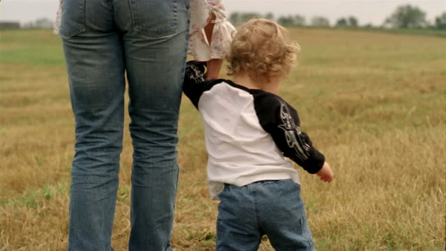 Medium shot baby boy holding hand of older girl and walking in field