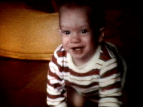 vídeos de stock, filmes e b-roll de 1972 medium shot baby crawling on hardwood floor/ close-up baby's face - engatinhando