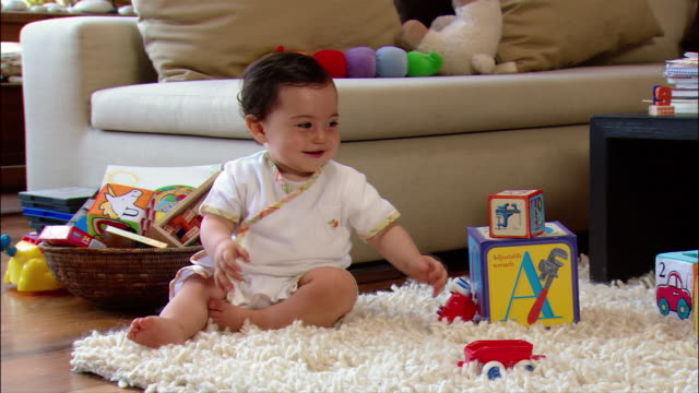 medium shot baby girl holding toy car / dropping toy and crawling across shag rug strewn with other toys - 生後6ヶ月から11ヶ月点の映像素材/bロール