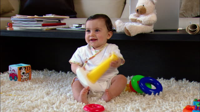 medium shot baby girl smiling and holding plastic ring toy on shag rug - 生後6ヶ月から11ヶ月点の映像素材/bロール
