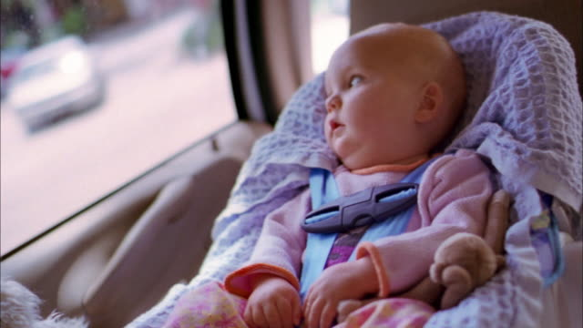 Medium shot baby in car seat looking out traveling car window