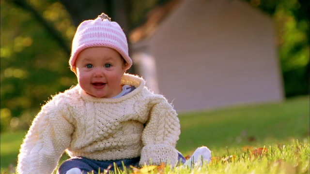 Medium shot baby in sweater and knit cap sitting + smiling outdoors