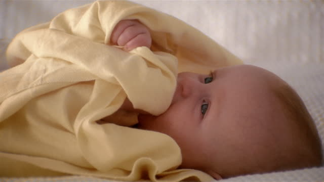 medium shot baby lying on back / wrapped in yellow blanket / sucking on blanket - one baby boy only stock videos & royalty-free footage