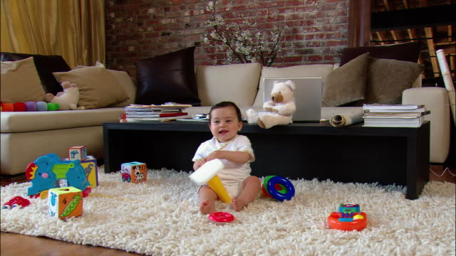 vidéos et rushes de medium shot baby playing with toys on shag rug in living room - bébés filles