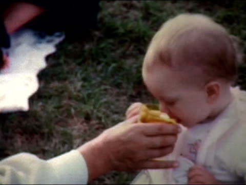 1972 medium shot baby sitting on grass, taking drink from cup - picnic stock videos & royalty-free footage