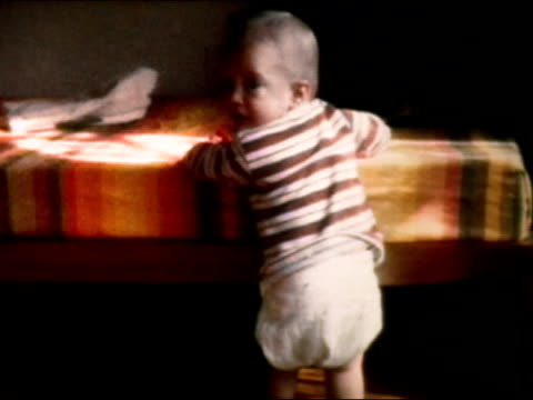 vidéos et rushes de 1972 medium shot baby standing up, holding onto bed, looking over shoulder - bébé de 0 à 6 mois
