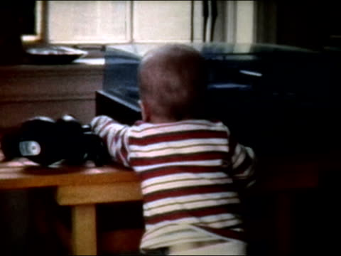 1972 medium shot baby standing up next to turntable, looking at cassette tape - cassetta video stock e b–roll