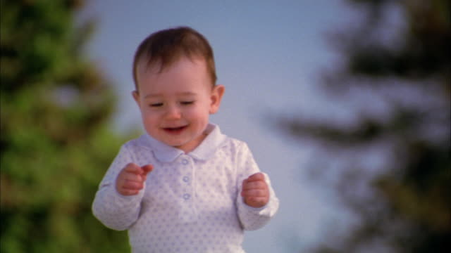 Medium shot baby taking first steps outdoors / smiling and waving arms