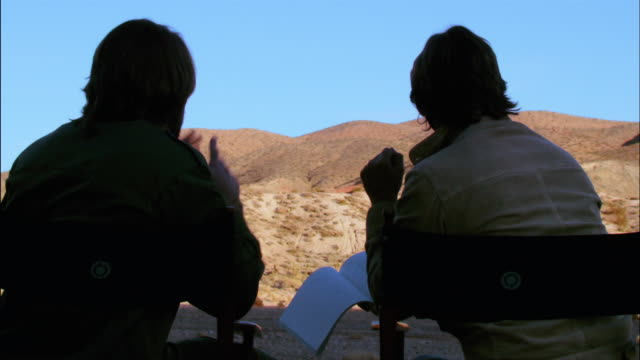 Medium shot backlit director and cinematographer discussing shot with desert landscape in background / Red Rock Canyon State Park, California